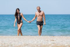 Attractive couple come from sea holding hands. Attractive couple at the sea. Young men in black swimming trunks and women in one-piece swimsuit come from sea Royalty Free Stock Photo