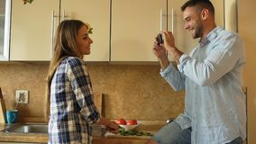 Attractive couple cooking in the kitchen and taking photo using smartphone fo sharing social media at home Royalty Free Stock Images