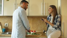 Attractive couple cooking in the kitchen and taking photo using smartphone fo sharing social media at home Royalty Free Stock Photos