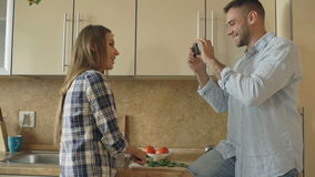 Attractive couple cooking in the kitchen and taking photo using smartphone fo sharing social media at home. In the morning stock video
