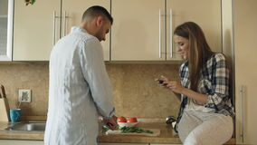 Attractive couple cooking in the kitchen and taking photo using smartphone fo sharing social media at home. In the morning stock footage
