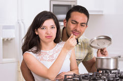 Attractive couple cooking together unpleasant meal. Unhappy husband trying unpleasant food that his wife prepared stock photos