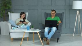 Casual couple networking with digital devices at home stock video
