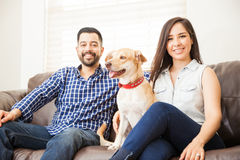 Attractive couple with a dog at home Royalty Free Stock Photos