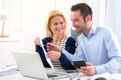 Attractive couple doing administrative paperwork. View of an Attractive couple doing administrative paperwork royalty free stock images