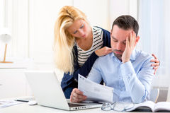 Attractive couple doing administrative paperwork. View of an Attractive couple doing administrative paperwork royalty free stock photography