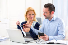 Attractive couple doing administrative paperwork. View of an Attractive couple doing administrative paperwork royalty free stock photo