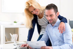 Attractive couple doing administrative paperwork. VIew of a Young attractive couple doing administrative paperwork Stock Photography