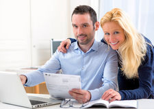 Attractive couple doing administrative paperwork. VIew of a Young attractive couple doing administrative paperwork stock photo