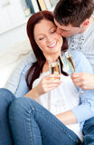 Attractive couple drinking champagne lying on sofa Stock Photos