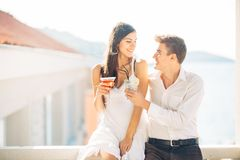 Attractive couple drinking cocktails ,enjoying summer vacation.Smiling,attracted to each other.Flirting and seduction. Man approaching to a woman.Boyfriend and royalty free stock images