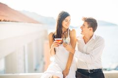 Attractive couple drinking cocktails ,enjoying summer vacation.Smiling,attracted to each other.Flirting and seduction. Man approaching to a woman.Boyfriend and royalty free stock photography