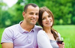 Attractive couple drinks wine in park Stock Photography
