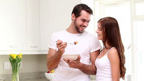 Attractive couple eating cereal in the morning stock video