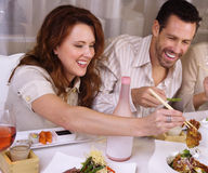 Attractive couple eating at restaurant,