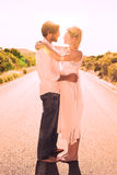 Attractive couple embracing barefoot on the road Royalty Free Stock Photos