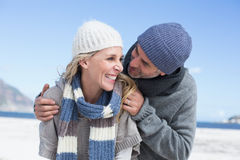 Attractive couple embracing on the beach in warm clothing Stock Photos