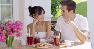 Attractive couple enjoying breakfast outdoors. Attractive young couple enjoying breakfast outdoors in the summer sunshine on an open air patio chatting and stock video