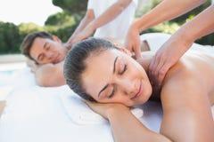 Attractive couple enjoying couples massage poolside