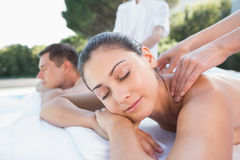 Attractive couple enjoying couples massage poolside Royalty Free Stock Photography