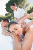 Attractive couple enjoying couples massage poolside Royalty Free Stock Image