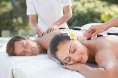 Attractive couple enjoying hot stone massage poolside Royalty Free Stock Photography