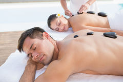 Attractive couple enjoying hot stone massage poolside Stock Photo