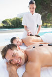 Attractive couple enjoying hot stone massage poolside Royalty Free Stock Photos