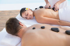 Attractive couple enjoying hot stone massage poolside Royalty Free Stock Photo