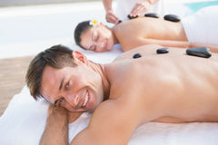 Attractive couple enjoying hot stone massage poolside Stock Images