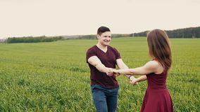 Attractive couple enjoying their time together, walking through a wheat field, holding hands, slow mo, steadicam shot stock video