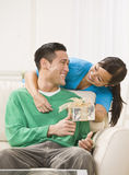 Attractive Couple Exchanging Gifts. An attractive young exchanging a gift. They are smiling directly at one another. Vertically framed photo stock photos