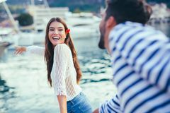 Attractive couple exploring on their summer vacation. Laughing as they hold hands while sightseeing a small boat harbour on the coast Stock Photography