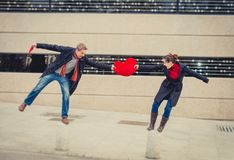 Attractive couple fighting over a love heart pillow Stock Photo