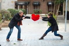 Attractive couple fighting over a love heart pillow Royalty Free Stock Photos