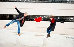 Attractive couple fighting over a love heart pillow Royalty Free Stock Photography