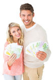 Attractive couple flashing their cash Royalty Free Stock Image