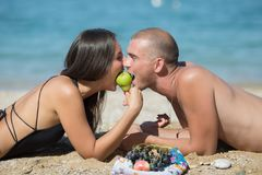 Guy and girl lie face to face together biting pear. Attractive couple flirting on beach. Guy and a girl lie face to face on sand and together biting pear stock image