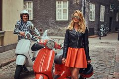 Attractive couple, a handsome man and female standing on an old street with two retro scooters. royalty free stock photos
