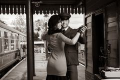 Attractive couple dance on railway station platform with portable record player royalty free stock photos