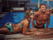 An attractive couple, handsome muscular male and woman relaxing near the pool after swimming. Enjoying vacation. royalty free stock photography