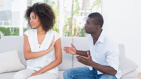 Attractive couple having an argument on couch Royalty Free Stock Photos