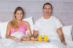 Attractive couple having breakfast in bed Stock Image