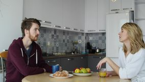 Attractive couple having breakfast together at home in the kitchen stock footage