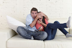 Attractive couple having fun at home enjoying watching television horror movie show. Young happy attractive couple having fun at home enjoying watching Royalty Free Stock Photos