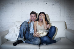 Attractive couple having fun at home enjoying watching television horror movie show Royalty Free Stock Image