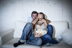 Attractive couple having fun at home enjoying watching television horror movie show Stock Photography