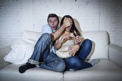Attractive couple having fun at home enjoying watching television horror movie show Stock Photo
