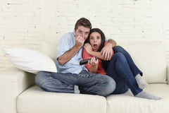 Attractive couple having fun at home enjoying watching television horror movie show. Young happy attractive couple having fun at home enjoying watching Stock Photos