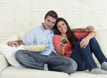 Attractive couple having fun at home enjoying watching television horror movie show. Young happy attractive couple having fun at home enjoying watching Stock Images